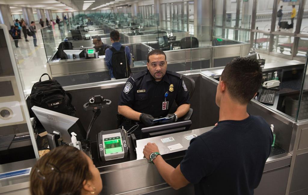 Un agent de la CBP passant en revue un couple de voyageurs